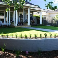 Curved brick wall retaining levelled lawn area.
