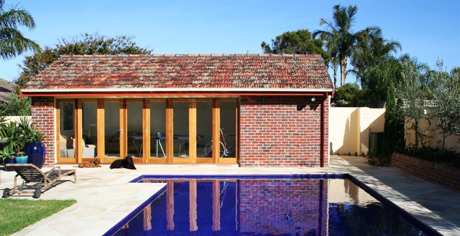 Surburban oasis garden in Melbourne, old garage converted into cabana with bathroom facilities and outdoor kitchen.  The existing pool was re-tiled and sandstone paving laid to match existing.  Large glazed terracotta pots placed to highlight focal areas from the main residence.  tropical pool landscaping, pool landscaping plants, landscaped pools, pool and landscaping.