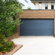 Exposed aggregate driveway, with brick retaining wall to match house.