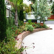 Exposed aggregate driveway, with brick retaining wall to match house planted in a Mediterranean style.