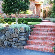 brick stairs, dry stone rock retainer wall, exposed aggregate driveway, turf, plant selection and planting, lighting