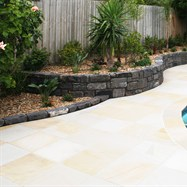 Bluestone retaining wall, contrasting will sandstone paving.