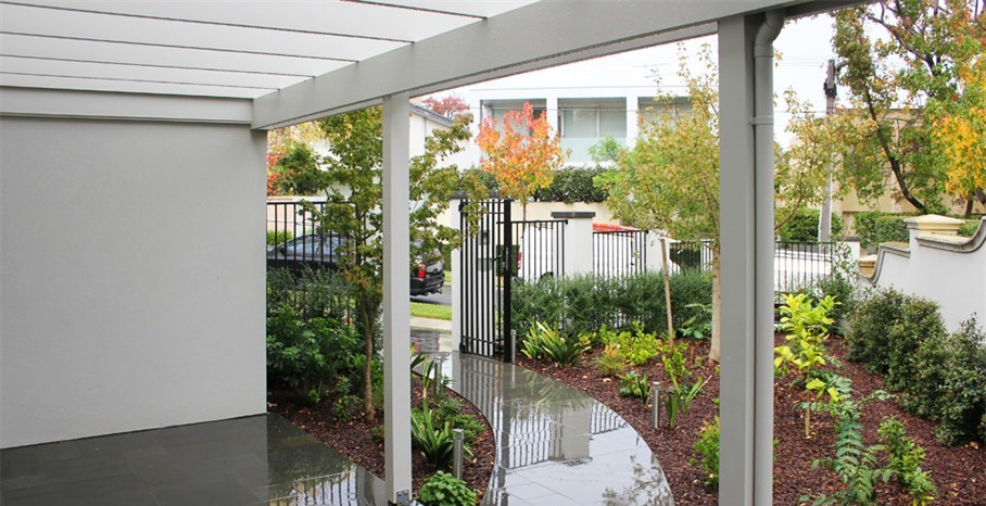 Cohesion garden design in Melbourne, random rectangular paving entrance with wrought iron fence and gates.  Planted as too soften building lines. Modern garden design, modern gardens, modern garden design ideas, garden makeover.